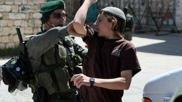 A Jewish settler argues with an officer as Israeli forces evict settlers from a house in Hebron, West Bank, on Wednesday.
