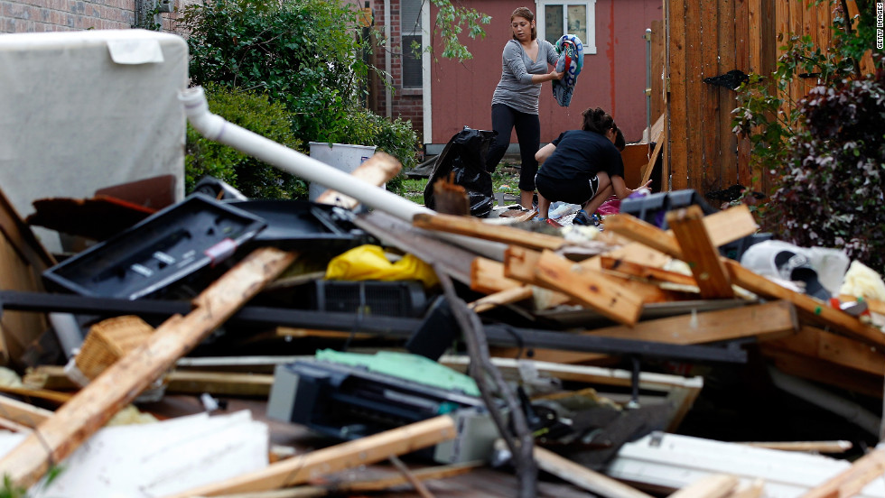 Residents search for personal belongings after a tornado destroyed their home in Arlington.