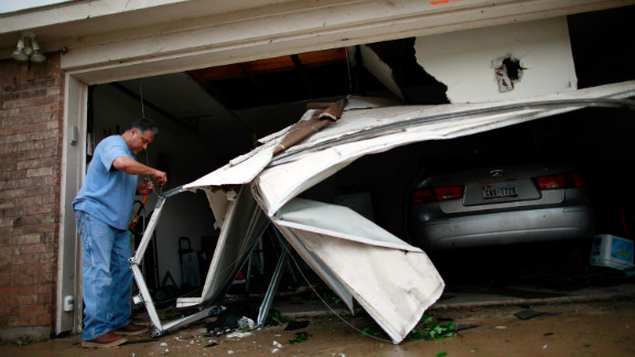 A man in Arlington works to clean up his garage after it was damaged by a tornado.