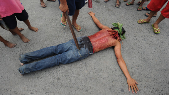 A penitent lies on the ground on the eve of the Good Friday re-enactments of the crucifixion of Jesus Christ in San Fernando City, north of Manila, Philippines. Despite the church