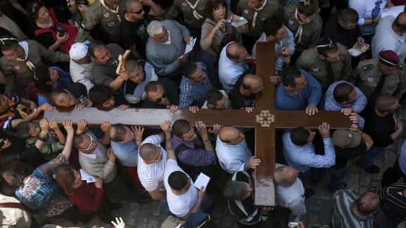 Christian Arab worshipers carry a large wooden cross along the Via Dolorosa, or the Way of Suffering, as they enter the Church of the Holy Sepulchre, an ancient, sprawling shrine that Orthodox and Catholic Christians believe was built on the original site of the crucifixion.