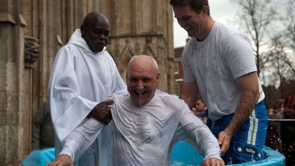 Archbishop of York John Sentamu, left, baptizes a local churchgoer during an Easter ceremony Saturday in York, England. The baptism of adults by total immersion is a ritual signifying the death of a believer