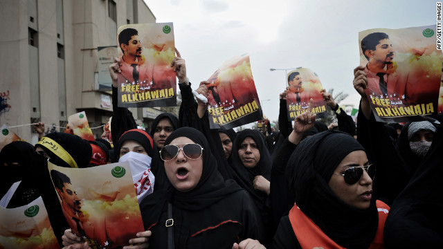 Bahraini Shiite demonstrators hold posters of jailed activist Abdulhadi al-Khawaja during a protest Friday.