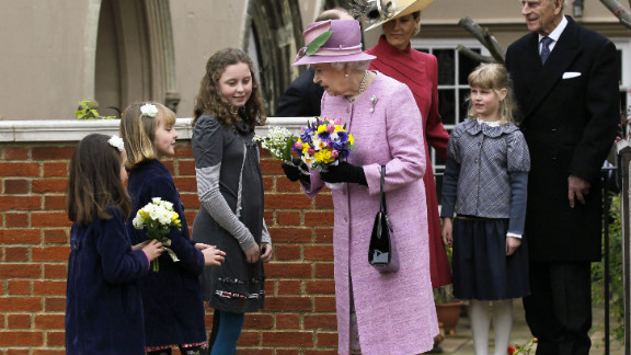 Queen Elizabeth II receives flowers from young people while her husband, Prince Philip, Duke of Edinburgh, daughter-in-law, Sophie, Countess of Wessex, and granddaughter Lady Louise Windsor look on as they leave Saint George