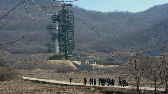 North Korean officials and foreign journalists leave the launch pad after a visit to see the rocket Unha-3 at the space center on April 8.
