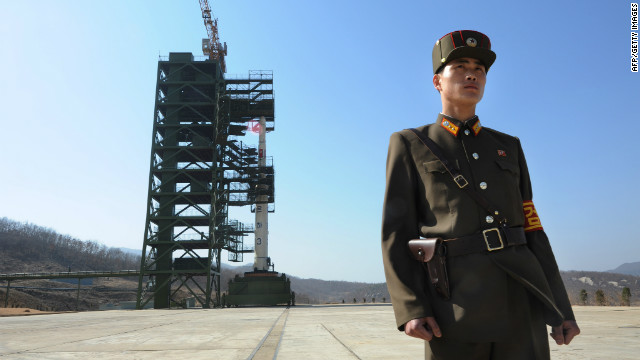 A North Korean soldier stands guard in front of a rocket that is being readied for launch