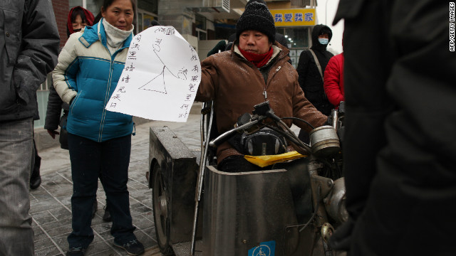 A man holds a placard calling for justice in the trial of Chinese rights activist Ni Yulan outside a courthouse during Ni's trial, in Beijing on December 29, 2011.