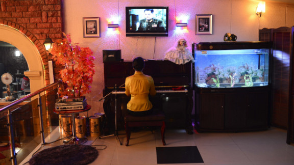 A woman plays the piano and entertains in a downtown Pyongyang restaurant. U.S. President Obama said the real consequence for North Korea, should it go through with the launch, is that the country