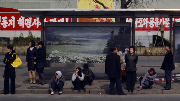 People line the street as they wait for a bus.