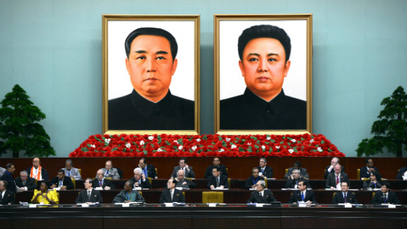 A portrait of late late Korean President Kim Il Sung (L) and his son, late leader Kim Jong Il hang of the wall as delegates take part in the World Congress of the Juche Idea in Pyongyang on April 12, 2012.
