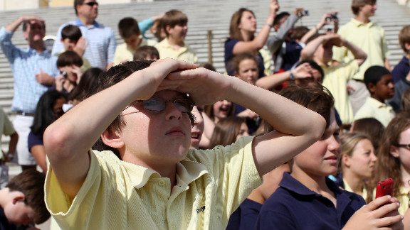 Schoolchildren on a tour watch as Discovery flies over the U.S. Capitol on Tuesday.