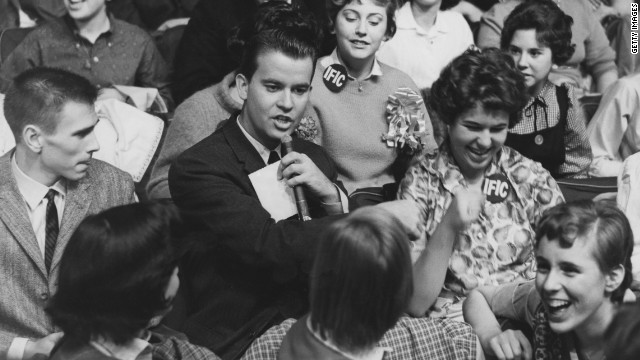 """American Bandstand""  host Dick Clark, pictured in 1958, surrounded by audience members."