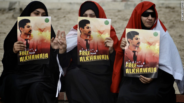 Bahraini demonstrators hold posters of Abdulhadi al-Khawajah, one of 13 defendants accused of attempting a coup.