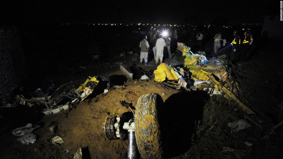 A plane wheel, center, lies amid debris at the scene of a plane crash as Pakistani rescue workers search for victims in the outskirts of Islamabad.