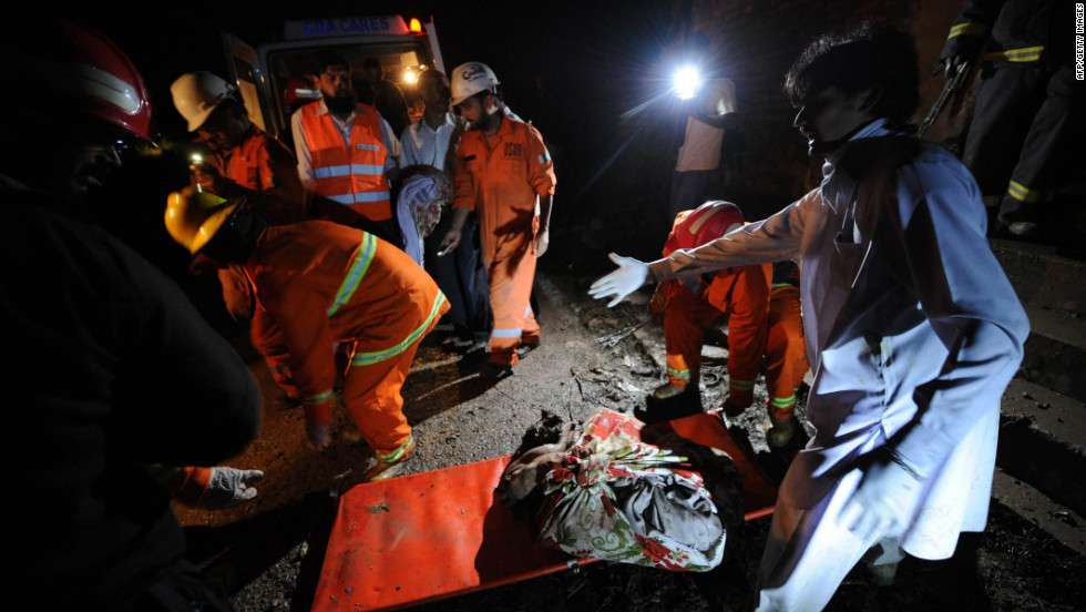 Pakistani rescue workers remove the covered remains of crash victims.