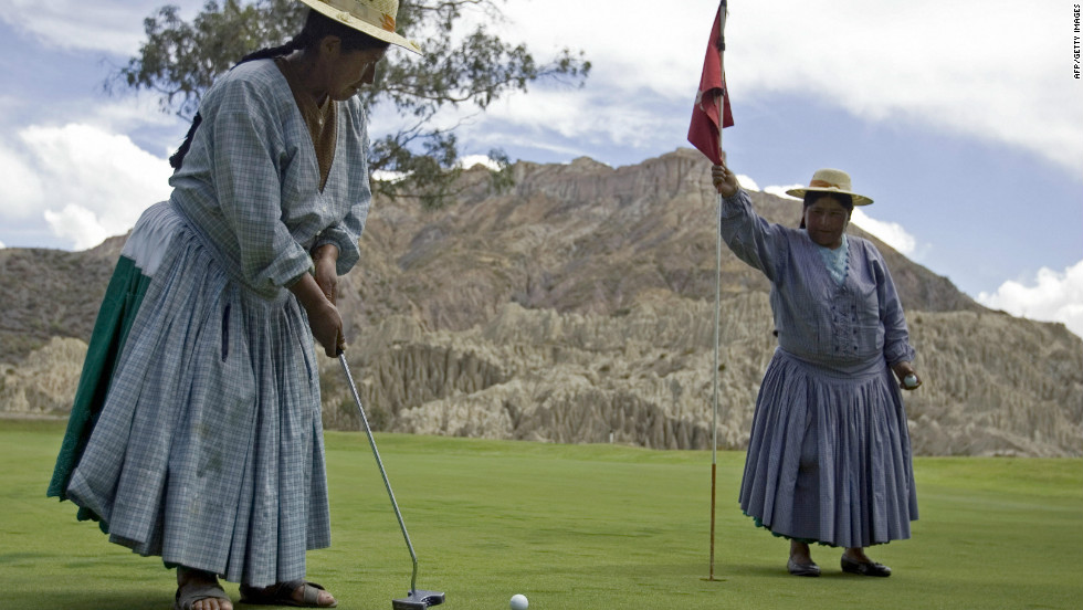 An  indigenous Aymara woman plays an approach shot as her colleague holds the flag.
