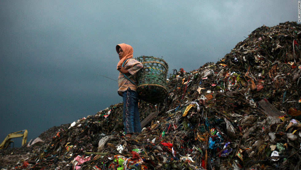 Eleven-year-old Nung, stands on the mountain of rubbish where she will collect plastic, at the Bantar Gebang landfill site, one of Jakarta's biggest dump sites. Around 6,000 metric tons of garbage is dumped daily at the landfill site, which will continue for the next 20 years, following the renewal of the site's contract in 2009.
