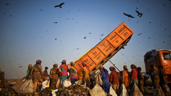"""""""Rag pickers"""" wait as a truck delivers garbage at the 70-acre Ghazipur Landfill site. They will sort through it picking out recyclable materials to sell. Delhi is estimated to have between 80,000 and 100,000 rag pickers who remove around 1,200-1,500 tons of trash from the municipal disposal chain each day. These activities, carried out in an ad-hoc way have unfavourable environmental, occupational health and community health implications."""