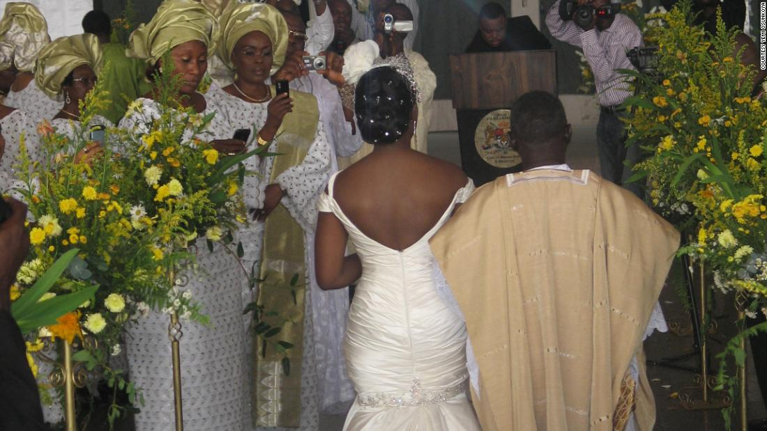 A Nigerian couple make their way up the aisle, with the bride wearing a white gown and the groom in traditional attire.