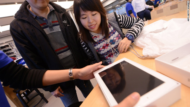 A woman smiles as her new iPad is presented to her at the Hong Kong Apple Store on March 16, 2012.