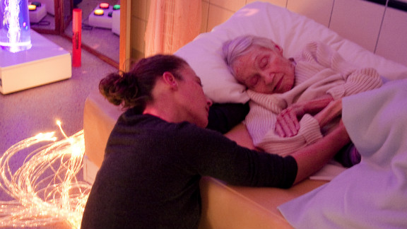 """Jacqueline, a French Alzheimer's patient, needs help getting into bed. Caregiver Cossève wraps her in a soft blanket. <a href=""""http://www.pace.edu/lovelosslaughter"""" target=""""_blank"""" target=""""_blank"""">Greenblat's images were on display </a>at New York's Pace University."""