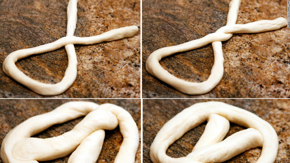 Begin by arranging each rope into a simple oval, crossing one end over the other. Then, flip the knot under once more. Bring the ends to rest at the top of the small oval shape, pinching them in so they'll stay secure. Then, flip the pretzel over, so the pinched ends are resting on the bottom.