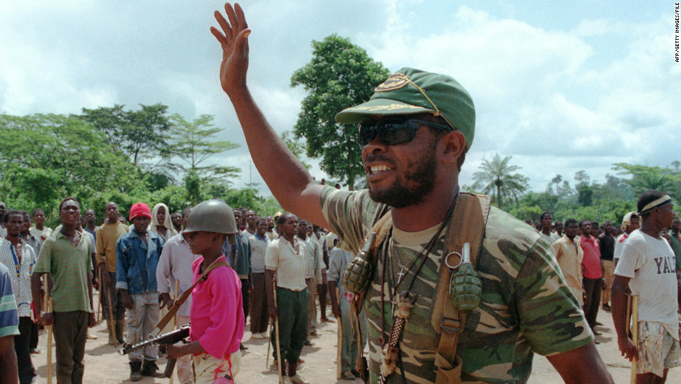 Charles Taylor, leader of the rebel National Patriotic Front of Liberia (NPFL) waves to recruits 28 May 1990 upon seizing the port of Buchanan, 200 kms (120 miles) from the capital Monrovia.