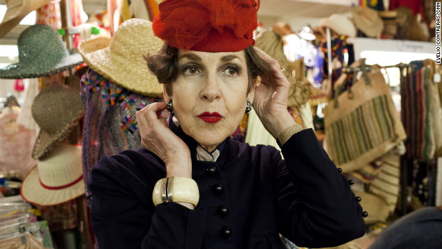 "Tziporah Salamon, 62, looks at herself in a mirror as she tries on a new hat at the Manhattan Vintage Clothing Show. ""All a girl needs is a hat,"" she says."
