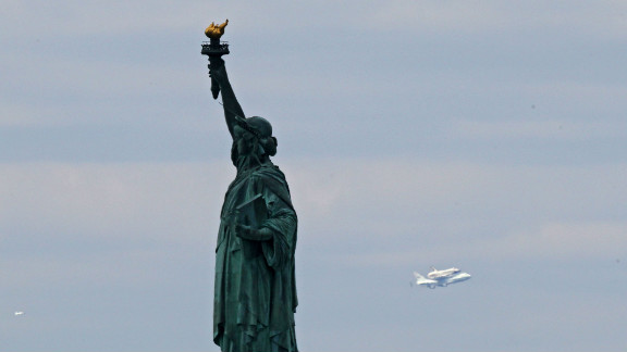 The Enterprise passes the Statue of Liberty into New York on the last leg of its final flight Friday.