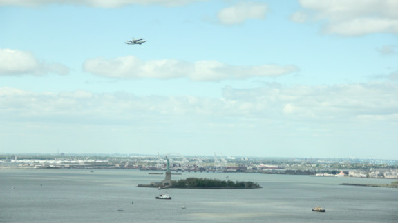 "Vijay Lorick captured this image of the shuttle over the Statue of Liberty from the 27th floor of his office building in downtown New York. ""Since Monday we've been trying to figure out when it's coming since we do have a great view,"" he said."