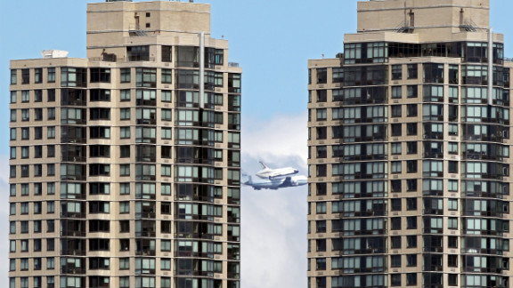 The space shuttle flies past the Jersey City skyline on the last leg of its final flight Friday.