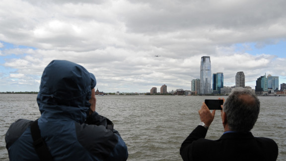 People photograph the Enterprise as it flies by the New Jersey skyline Friday.