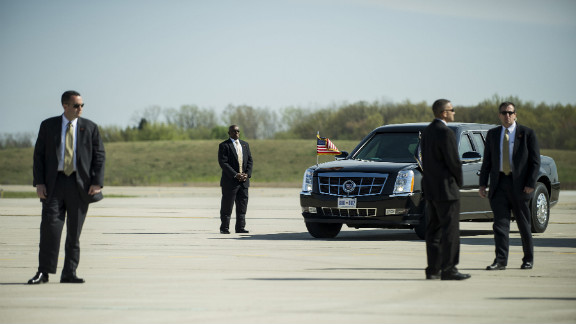 Members of the Secret Service await the arrival of President Barack Obama at the Detroit airport.