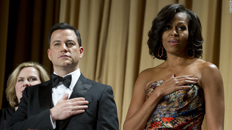 Host Jimmy Kimmel stands alongside first lady Michelle Obama while the national anthem is played.
