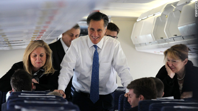 Mitt Romney and his wife Ann Romney talk to members of his staff aboard his campaign plane in March.