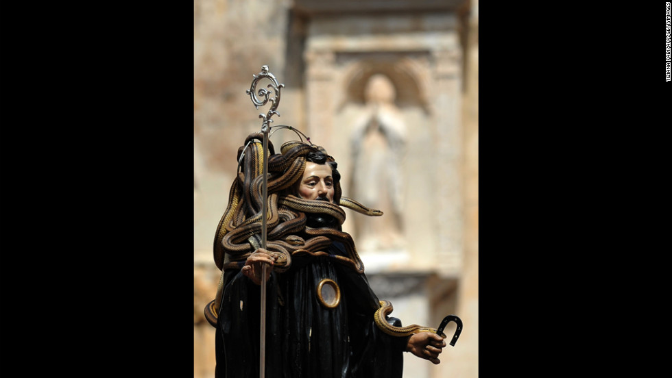 Worshippers hold up a statue Tuesday of San Domenico (St. Dominic) wrapped in snakes during an annual procession in Cocullo, in the Abruzzo region of Italy.