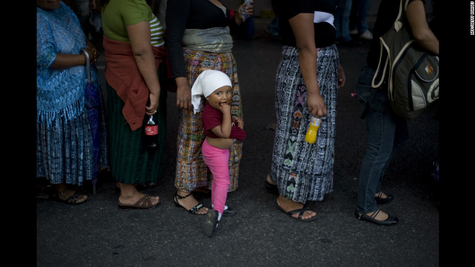 A girl walks with women as members of various labor unions take part in a rally for International Labor Day Tuesday in Guatemala City, Guatemala.