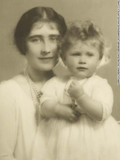 A little princess, Elizabeth II sits with her mother Queen Elizabeth.