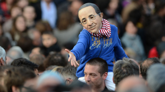 A boy wearing a mask resembling Francois Hollande gestures before the politician's speech Sunday.