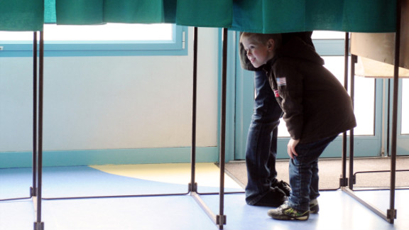 A child looks under the curtain of a voting booth in Henin-Beaumont, France, near the border with Belgium.