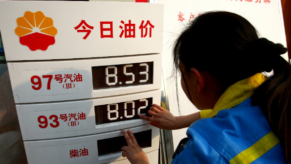 A worker changes the price panel at a petrol station in Suining, southwest China