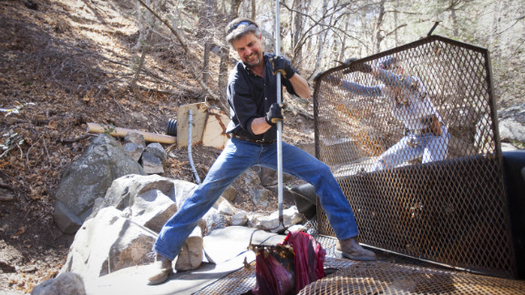 Rudd pulls a discarded jacket from one of Tombstone's springs in Carr Canyon near Sierra Vista. Tombstone city employees frequently have to drive into the mountains to check the springs for leaks, debris and vandalism.