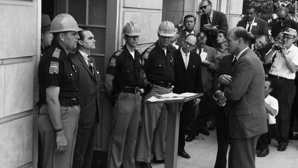 Federal Deputy Attorney General Nicholas Katzenbach, standing on the right, confronts Alabama Gov. George Wallace at the University of Alabama in Tuscaloosa on June 11, 1963. Wallace is standing in the doorway to prevent two African-American students from entering despite a presidential order. Wallace, who was pro-segregation, later stood aside.