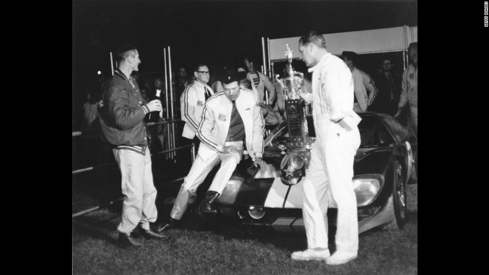 Shelby sits on the front of his Ford GT-40 after drivers Ken Miles, left, and Lloyd Ruby drove it to victory in the Daytona Continental in 1965.