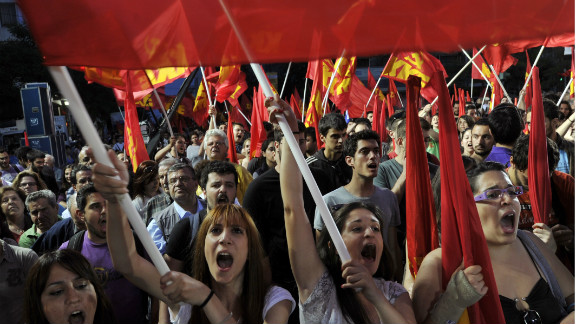 Supporters of the Greek Communist Party waves party flags and chant slogans, during a rally calling for Greece