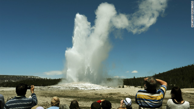 Tourists watch the Old Faithful geyser, which erupts on average every 90 minutes in Yellowstone National Park, Wyoming.