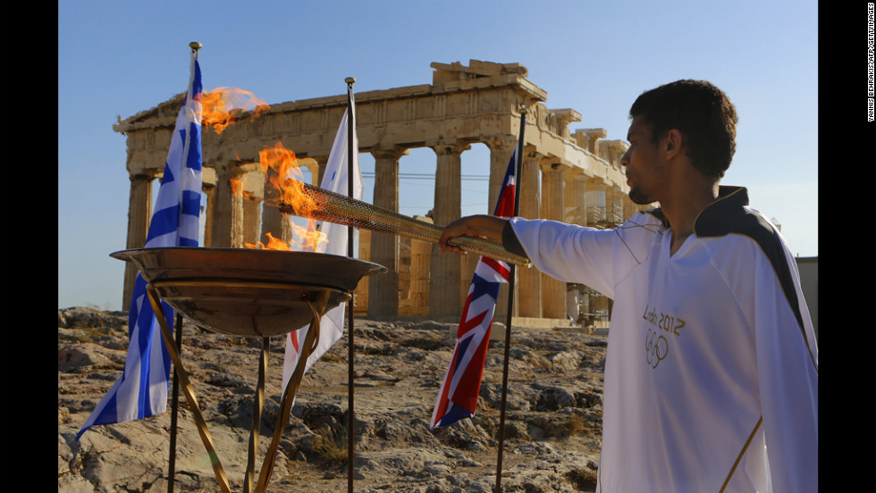 Torchbearer Dimitrios Chondrokoukis, a Greek high jump athlete, lights a cauldron with the Olympic Flame atop the Acropolis in Athens on Wednesday. The flame will be handed over to London Olympics officials on Thursday.