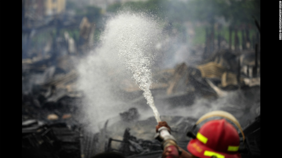 Bangladeshi firefighters control a blaze at a slum in Dhaka on Wednesday. The fire destroyed more than 1,000 homes.