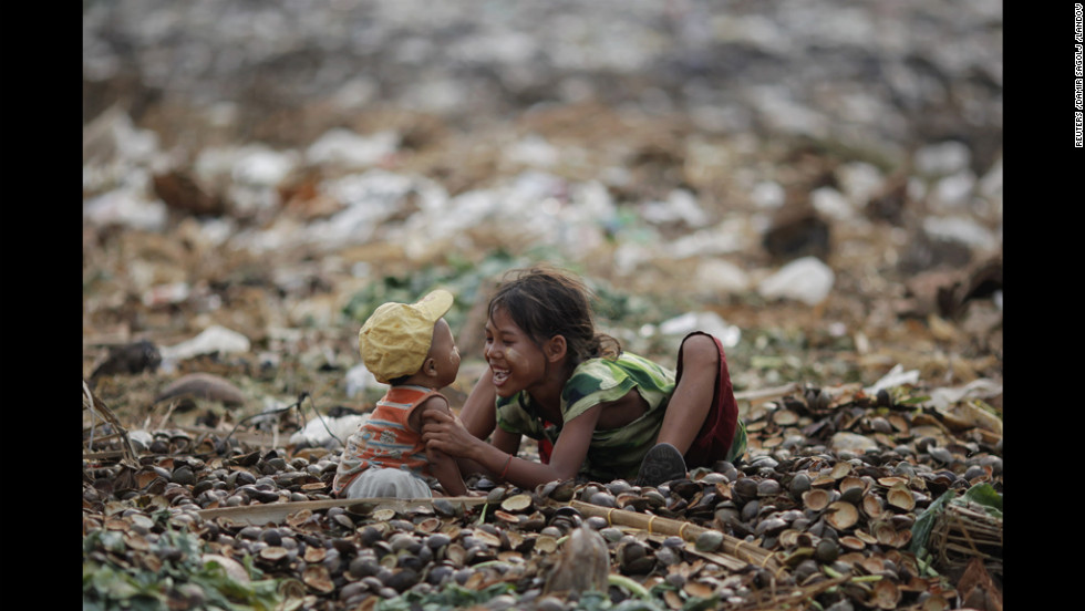 A girl plays with her brother as they search for usable items Wednesday at a junkyard near the Danyingone station in the suburbs of Yangon, Myanmar.