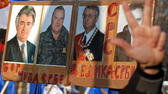 "Serb nationalists protest against the U.S. and the U.N. war crimes court in Belgrade in December 2006. Their posters show pictures of Karadzic, Mladic and Vojislav Seselj with the Cyrillic writing meaning: ""God saves the Serbs"" and ""Great Serbia."""